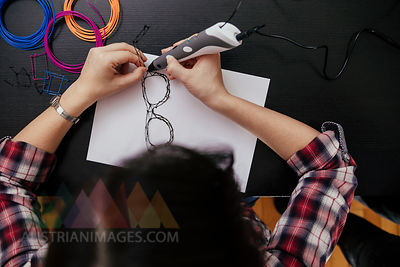 Young woman drawing spectacles with 3D pen