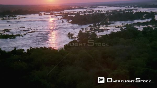 Aerial wide shot river with trees at sunset sunrise and sun reflecting on water Botswana