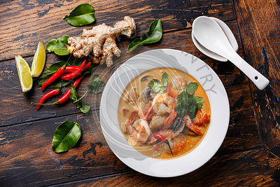 Tom Yam kung Spicy Thai soup with shrimp, seafood, coconut milk and chili pepper in bowl on wooden background