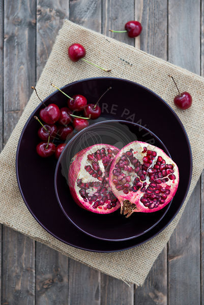 Pomegranate and cherries in a bowl.