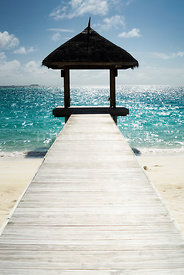 An atmospheric image of an empty wooden dock / boardwalk, on a tropical beach.