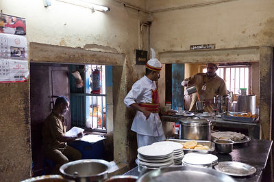 India - Kottayam - A waiter waits for tea to be poured for an order while the Supervisor checks the books in the kitchen of t...