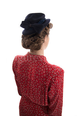 A 1940's woman in a red dress and hat, facing away – shot from other.