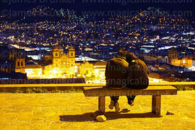 Couple looking at view over Plaza de Armas from Plaza San Cristobal at twilight, Cusco, Peru