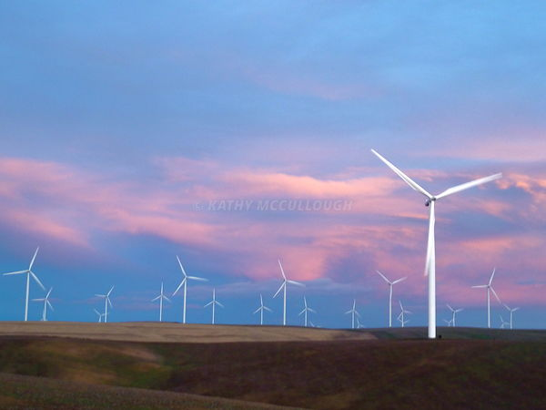 Wind towers at sunset over wheat stubble