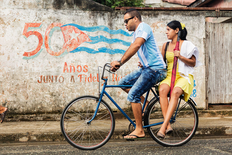 Couple on a Bicycle Riding Past Political Graffiti