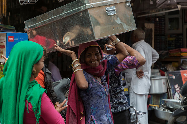 A Woman Carries a Metal Trunk on her Head in Jodhpur Street