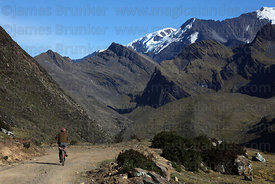 Local man cycling along dirt road , Cordillera Apolobamba , Bolivia