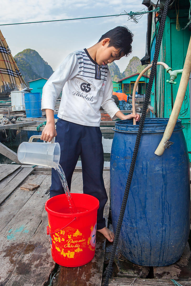 Tué , 12 ans, prépare un seau avec de l'eau bouillante et de l'eau froide afin d'avoir de l'eau tiède pour aller prendre sa douche, Baie de Lan Ha, Vietnam / Tué, 12 years old, prepares a bucket with boiling water and cold water to have warm water to go take a shower, Lan Ha Bay, Vietnam