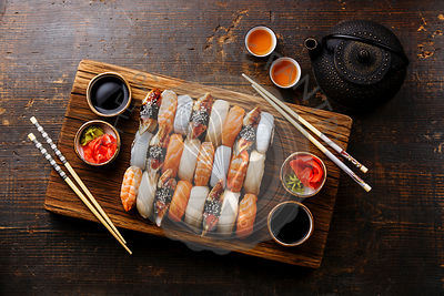Nigiri sushi set for two on wooden serving board block and green tea