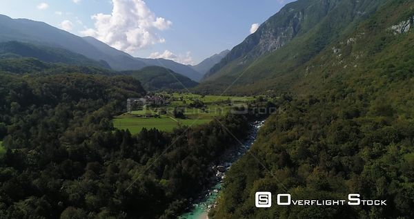 Mountain rapids, C4K aerial drone view over a turquoise river named soca, towards a small town, in the alpine nature, near Tr...