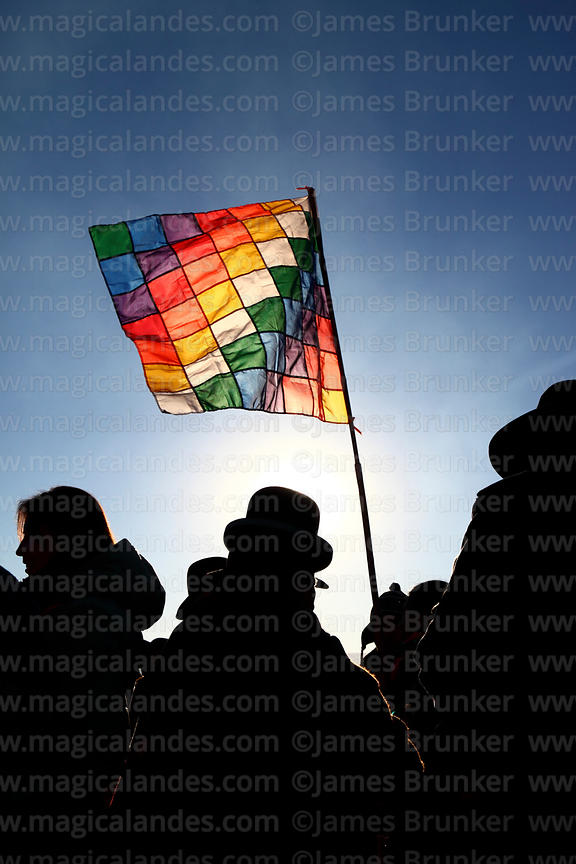 Aymara people carrying a wiphala flag silhouetted against the sun during Aymara New Year celebrations, Tiwanaku, Bolivia