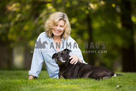 pit bull and owner sitting in grass smiling
