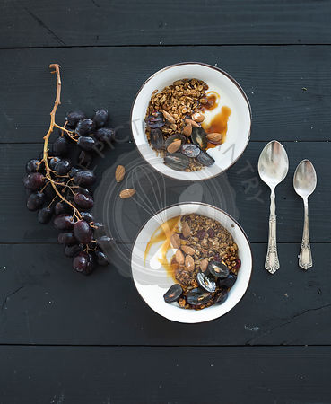 Healthy breakfast set. Bowls of oat granola with yogurt, fresh grapes, almond and  honey over black wooden backdrop