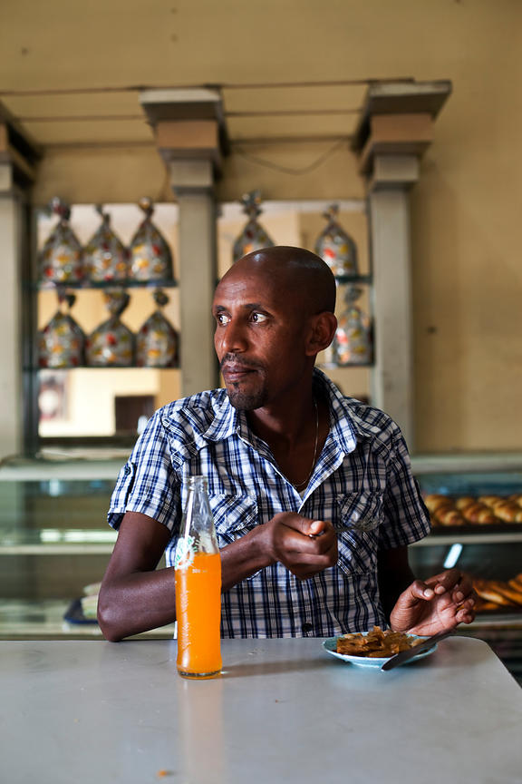 Ethiopia - Addis Ababa - A customer eats baklava in the Ras Makonnen coffee house
