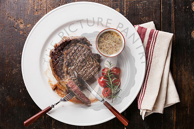 Sliced medium rare grilled Beef steak Ribeye with grilled cherry tomatoes and and Pepper sauce on white plate on wooden backg...