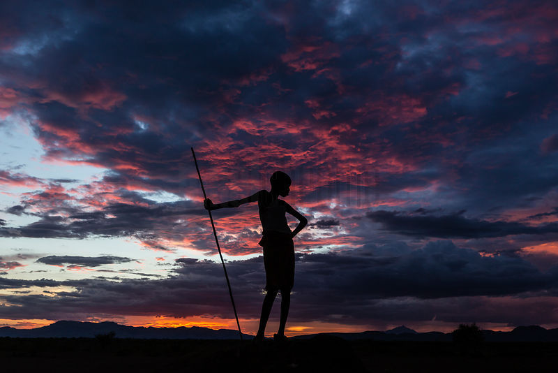 Silhouette of a Nyangaton Boy on an Anthill at Sunset