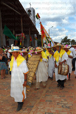 Musician playing Bajon Grande in front of church during main procession, San Ignacio de Moxos, Bolivia