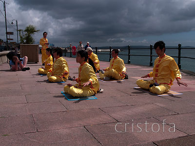 Falun Gong exercise under a stormy sky.