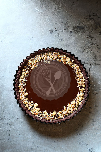Chocolate caramel tart topped with ground walnuts on a pan.Top view