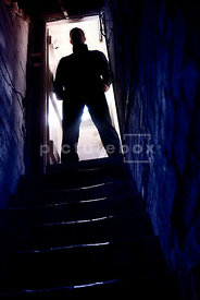 An atmospheric image of the silhouette of a mystery man at the top of some cellar steps.