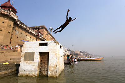 Boys swim and dive in the Ganges River, Peshwas Raja Ghat, Varanasi, India