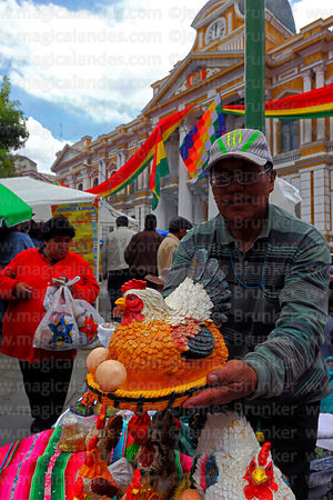 Vendor holding a ceramic chicken with eggs, Alasitas festival, La Paz, Bolivia