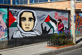 Girl walking past a mural showing support for Palestine, La Paz, Bolivia