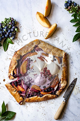 Peach and Blueberry Galette on a marble background