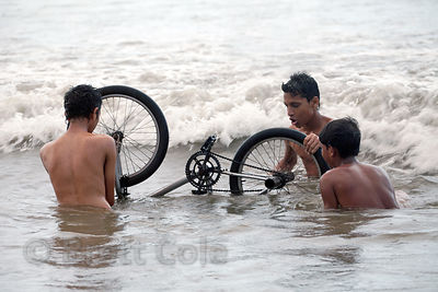 A group of men repair a bicycle in the Arabian Sea at Juhu Beach, Mumbai, India.