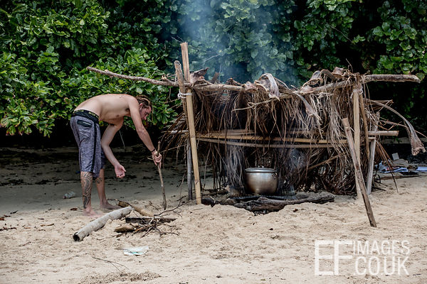 Man With Beach Cooking Fire On A Tropical Island