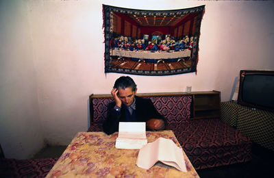 Albania - Thethi - Pashke Sokol Ndocaj reads family inheritance documents on her table
