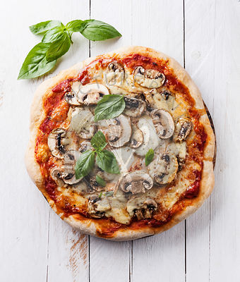 Pizza with mushrooms and basil on white wooden background