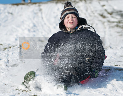 Young boy comes towards camera on a sledge