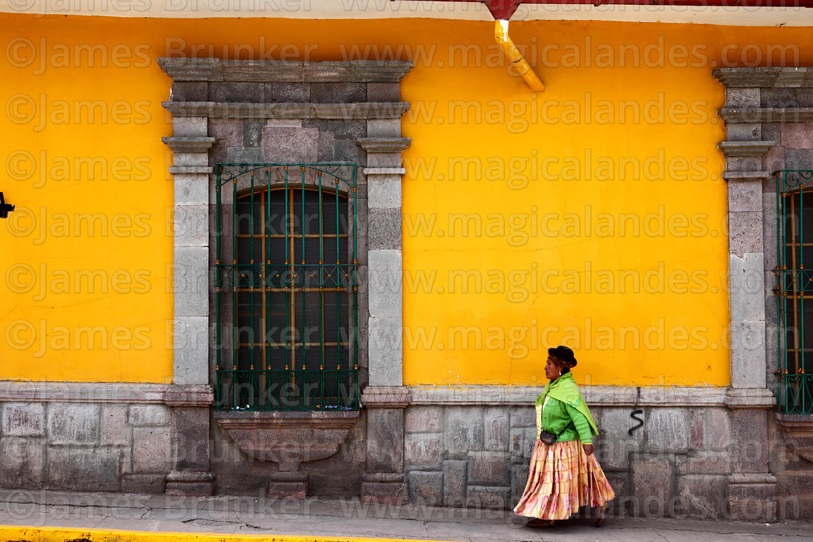 Aymara woman walking past colonial building, Puno, Peru