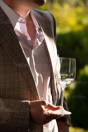 Gentleman holding a glass of white wine in a trendy dinner jacket