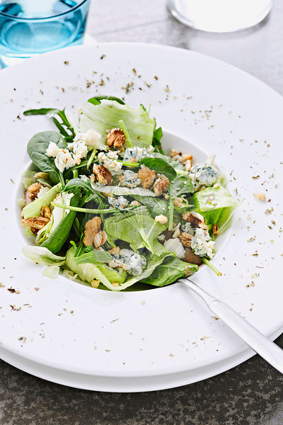 Close up shot of green salad with spinach and blue cheese