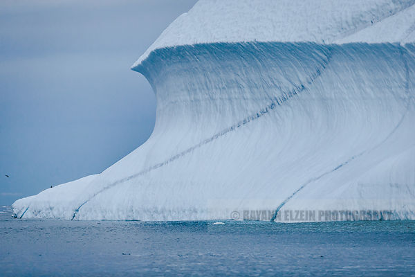 Iceberg with thin layer of ice spiraling on its side in Ilulissat