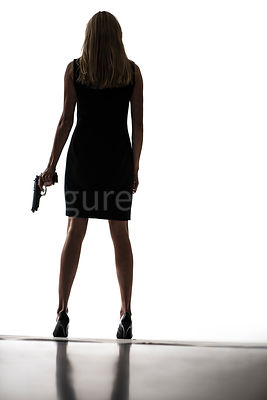 A silhouette of a woman standing with a gun – shot from low level.
