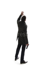 A semi-silhouette of a mystery man in a big coat, holding a gun and waving to a helecopter – shot from eye level.