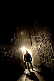 An atmospheric image of the silhouette of a mystery man walking down an alley at night.