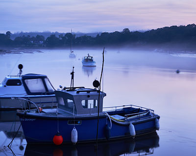 Misty conditions for the moored yachts and boats on a very calm morning along the banks of the Beaulieu River in the New Forest.