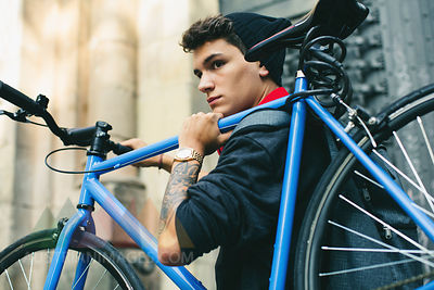 Teenager carrying fixie bike in the city