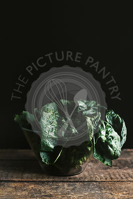 Fresh spinach in a bowl on a dark background