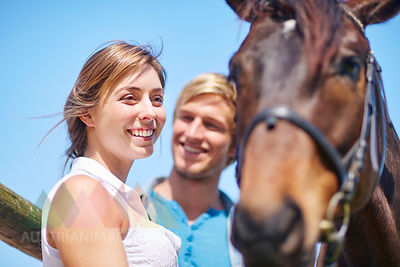 Happy young couple with horse