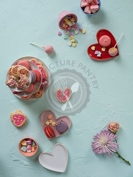 A colorful array of valentines sweets layed out on a mint green surface.