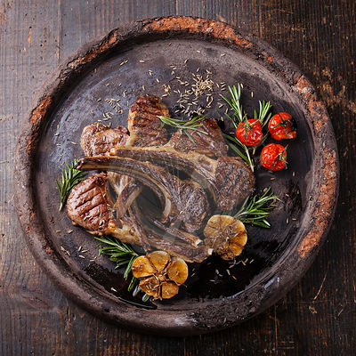 Roasted lamb ribs with spices and garlic on dark textural background