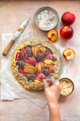 Preparing a stone fruit galette.Hand sprinkles almond flakes over the crust