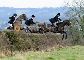 Laura Watts, William Fox-Grant jumping a hedge above Wilson's covert