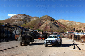 New Nissan Patrol driving past old steam engines at Pulacayo, Potosi Department, Bolivia